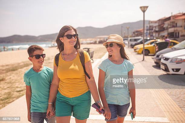 Mother walking with her children near the sea