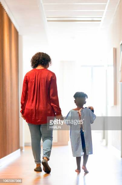 Mother walking with ill boy in hospital corridor