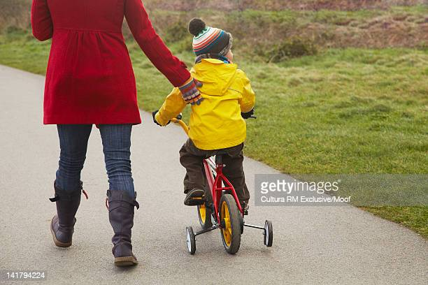 Mother walking with son on bicycle