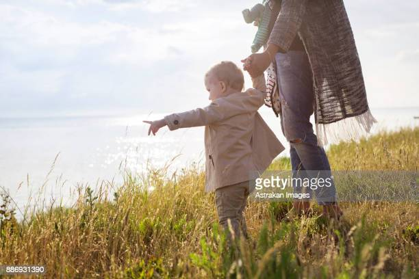 Mother walking with son (18-23 months) towards sea