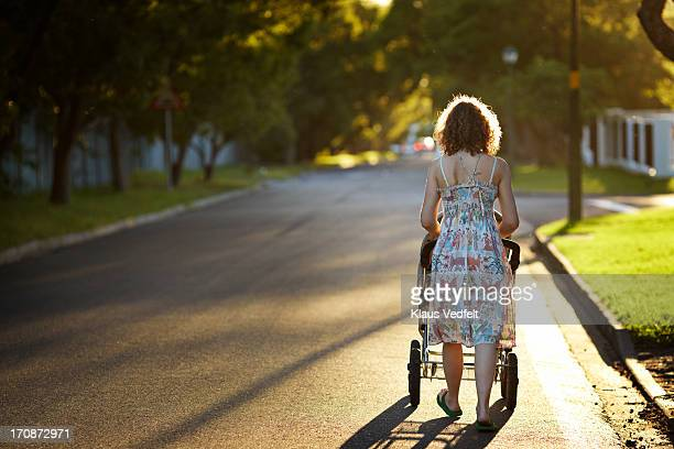 Mother walking with stroller in the sunset