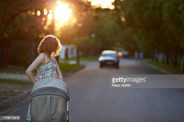 Mother walking with stroller looking back at car
