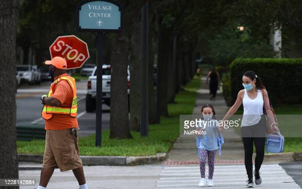 Mother walks her child to school on the first day of in-person classes in Orange County at Baldwin Park Elementary School on August 21, 2020 in...