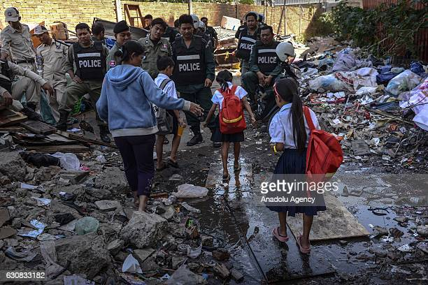 A mother walks her children to school as polices gather during a protest at the Borei Keila site in Phnom Penh Cambodia on January 3 2017 Families...