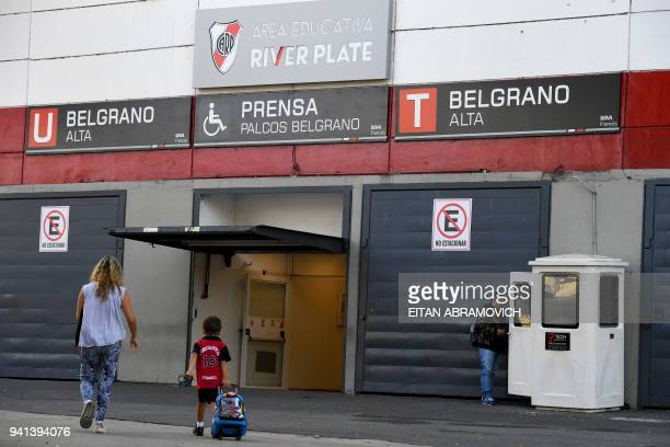 Mother walks his child to the school of Argentine football club River Plate, in Buenos Aires on April 3, 2018. Several youth players have reported...