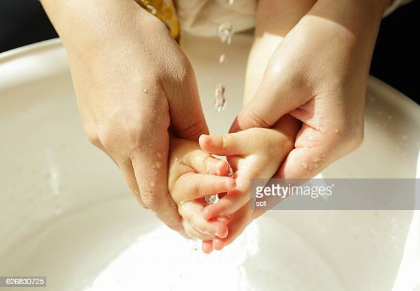 Mother washing hands of baby boy,close up