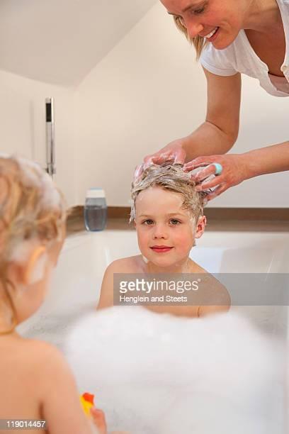 Mother washing sons hair in bathtub