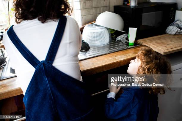 mother washing the dishes and her son helping her - single mother stock pictures, royalty-free photos & images