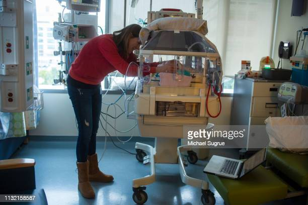 A mother watches her baby in an isolet with hyperbillirubinemia in the neonatal intensive care unit of a hospital.