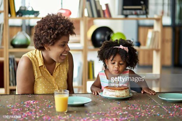 mother watching as 3 year old blows out birthday cake candle - number stock pictures, royalty-free photos & images
