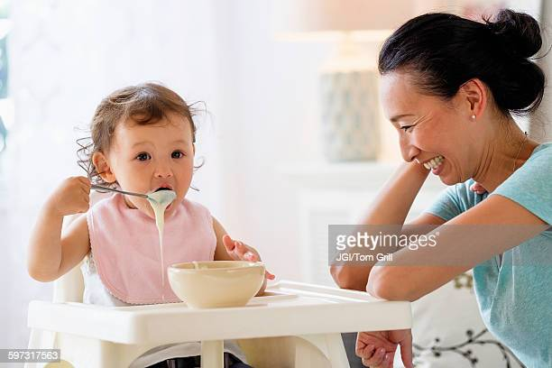 Mother watching baby daughter eat in high chair