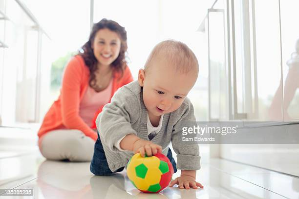 mother watching baby playing with ball - sports ball stock pictures, royalty-free photos & images