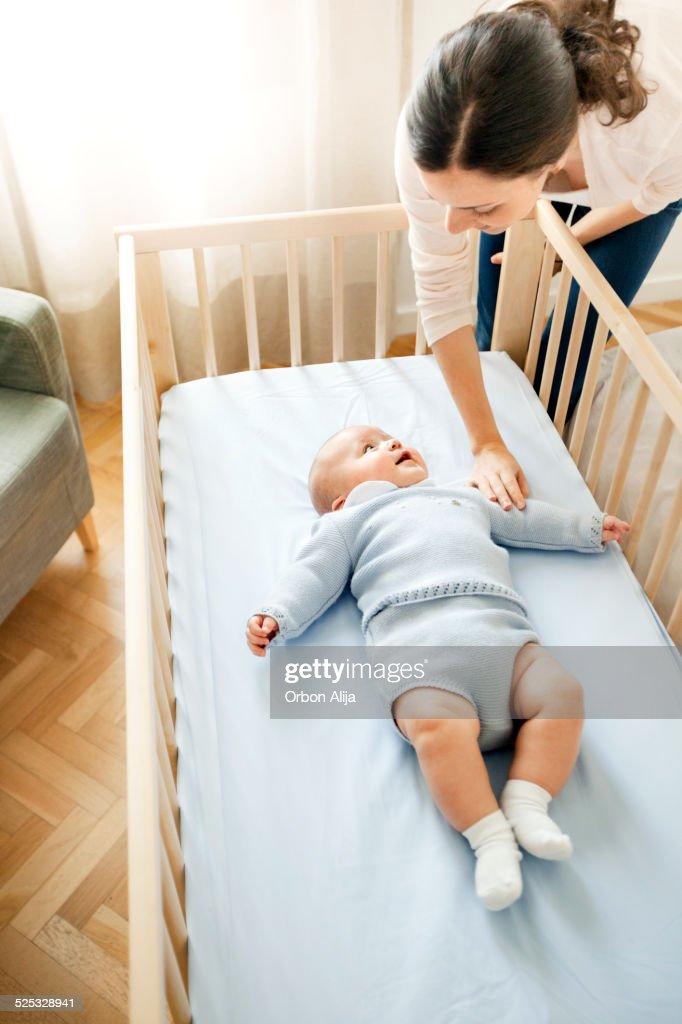 Mother watching baby sleep in his room : Stock Photo