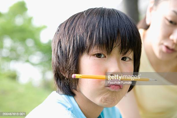 Mother watching boy (9-11) hold pencil between lip and nose
