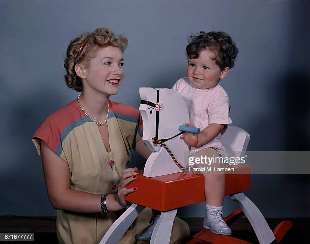 mother watching boy playing on rocking horse  - number of people stock pictures, royalty-free photos & images