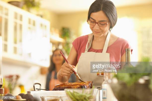 Mother watching daughter basting meat in domestic kitchen