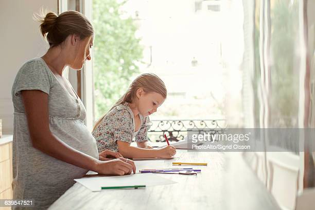 Mother watching daughter coloring