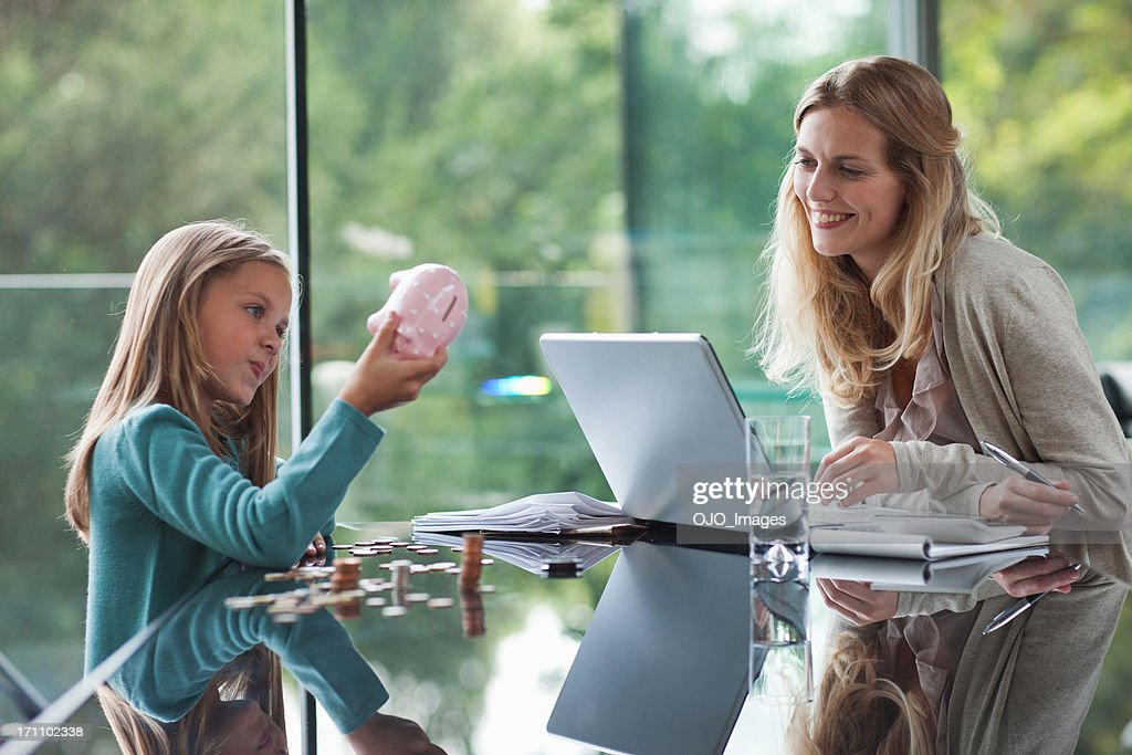 Mother watching daughter count coins from piggy bank : Stock Photo