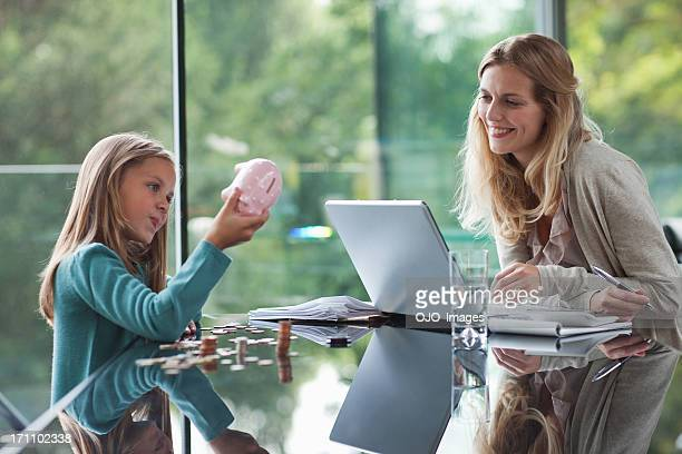 Mother watching daughter count coins from piggy bank