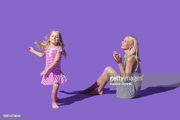mother watching daughter dancing on purple background - striped dress stock photos and pictures