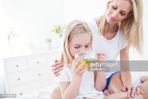 mother watching daughter drinking cup of tea on bed - unschuld stock-fotos und bilder