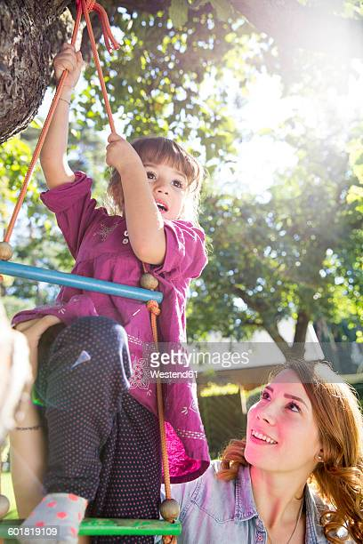 Mother watching daughter on rope ladder in garden