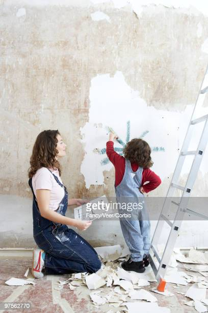 Mother watching daughter paint on wall