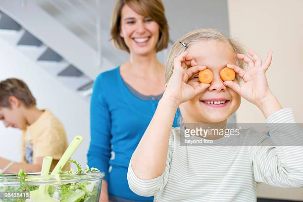 mother watching daughter playing with carrot slices in kitchen