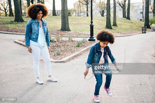 Mother watching daughter using skipping rope on pathway, smiling