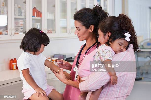 Mother watching doctor giving daughter injection
