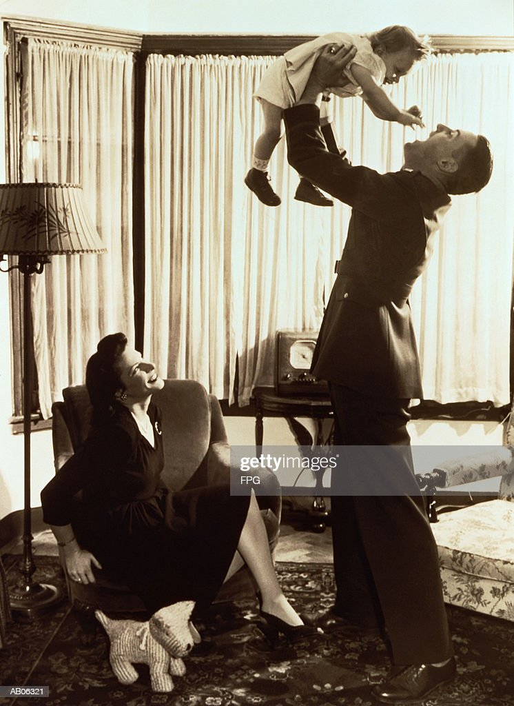 Mother watching father lifting toddler (18-21 months) (B&W sepia tone) : Stock Photo