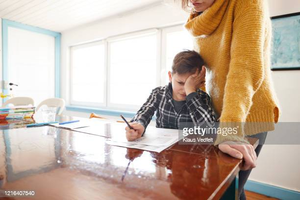 mother watching frustrated son doing homework at dining table - part of a series foto e immagini stock