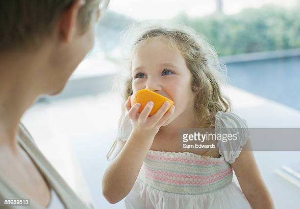 Mother watching girl eating orange
