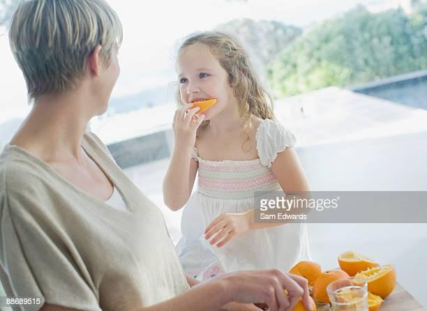Mother watching girl eating orange