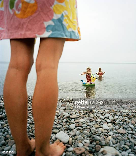 mother watching her children in the water oland sweden. - sea swimming stock photos and pictures