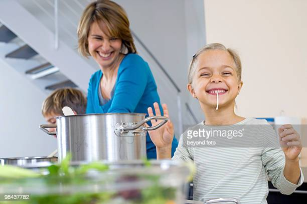 mother watching her daughter tasting spaghetti