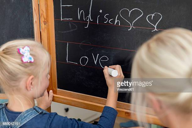 Mother watching her daughter writing the word love on blackboard