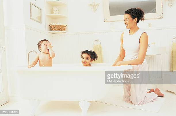 Mother Watching Her Son and Daughter Having a Bath