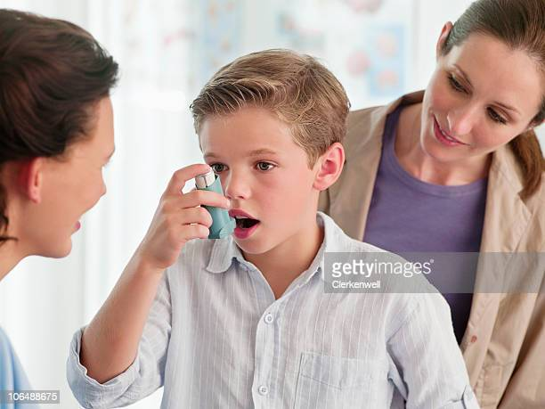 Mother watching nurse help boy (10-11) with an asthma inhaler