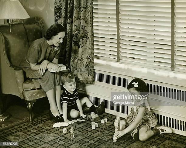 Mutter beobachten Sohn und Tochter spielen (4-5