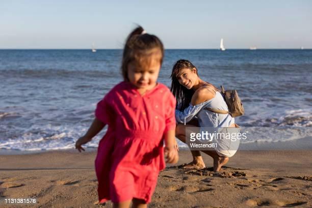 mother watching running daughter on he beach - sac porté épaule photos et images de collection