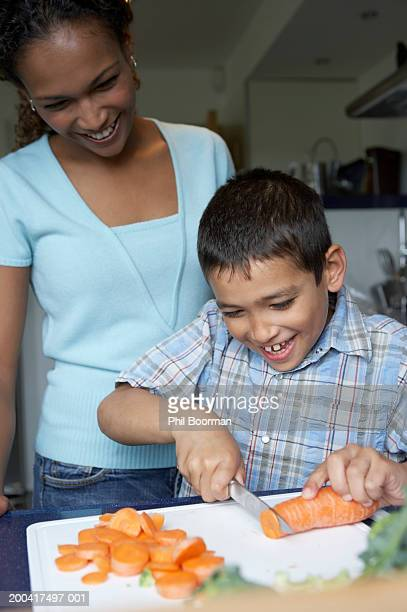 Mother watching son (8-10) chop carrots