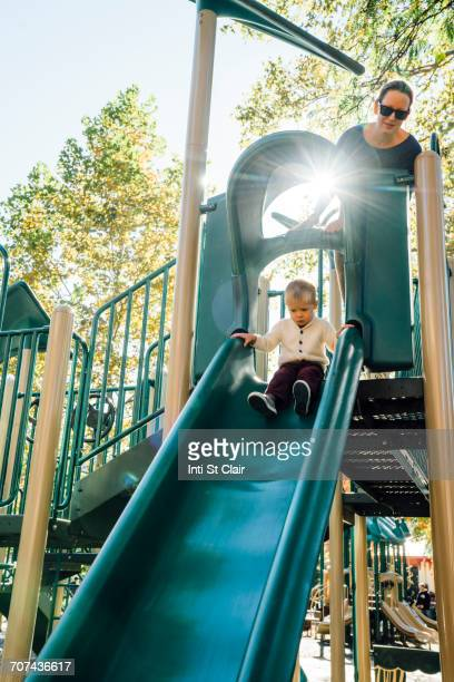 Mother watching son on playground slide