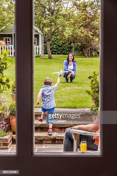 mother watching son play in garden with toy airplane - patio doors stock pictures, royalty-free photos & images