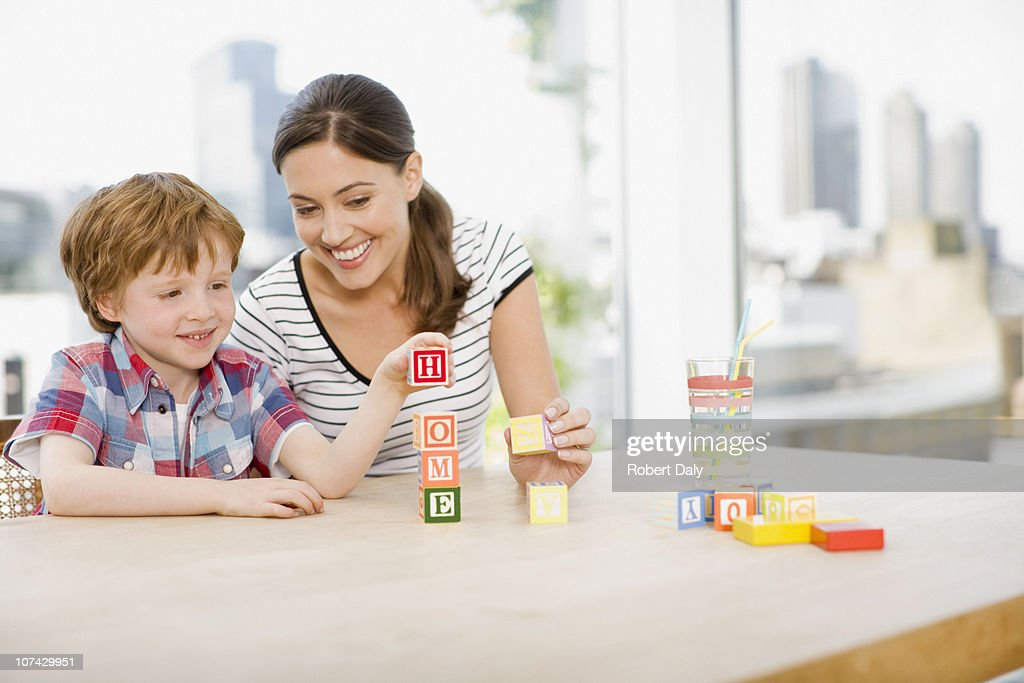 Mother watching son stacking alphabet blocks and spelling home : Stock Photo