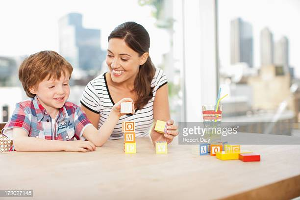Mother watching son stacking alphabet blocks and spelling 'home'