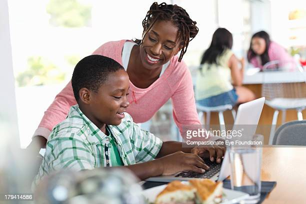 Mother watching son using laptop in kitchen