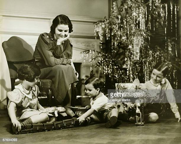 Mother watching three children playing by Christmas tree, (B&W)