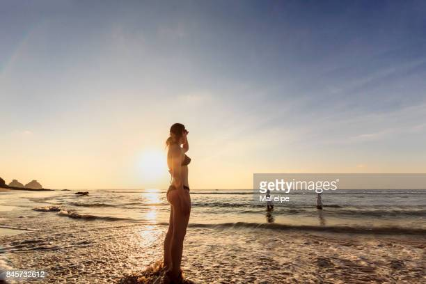 mother watchingr her daughters at deserted beach - tween girls hot stock photos and pictures