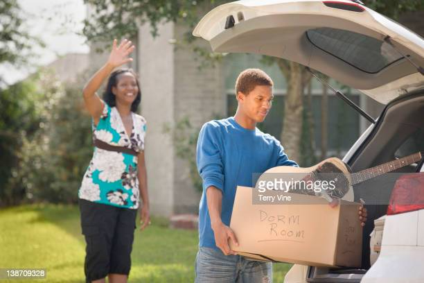 Mother waving at teenage son as he packs for college